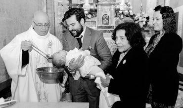 BABYBJÖRN Föräldramagasin – Dotterns dop i kyrkan, prästen häller vatten över hennes huvud.