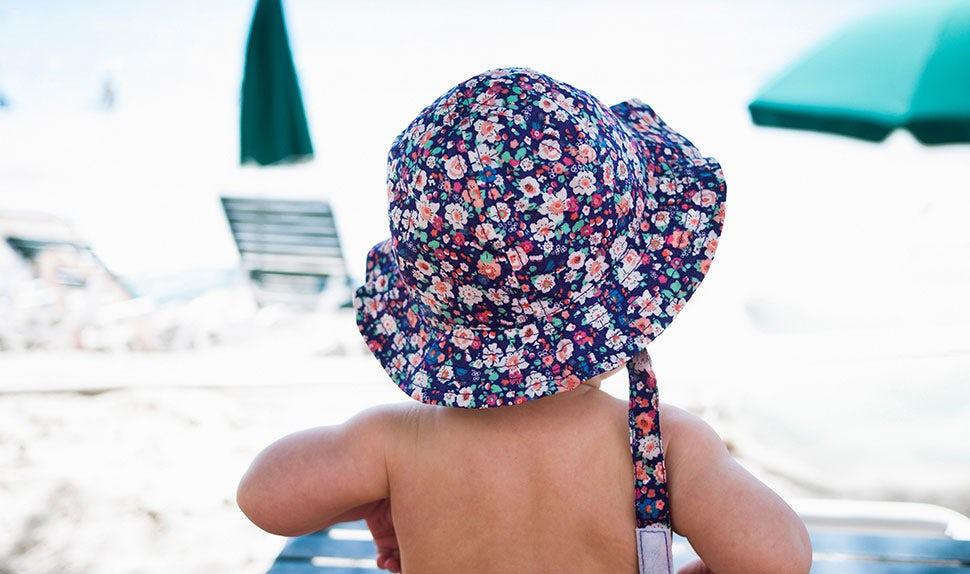 BABYBJÖRN Föräldramagasin – Barn på stranden i solhatt, att resa med bebis är spännande.