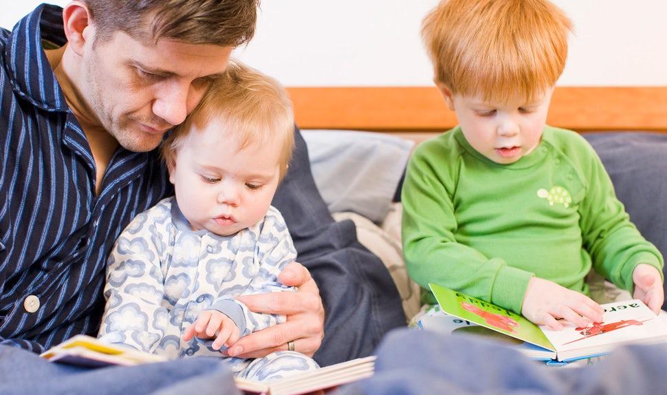 BABYBJÖRN Föräldramagasin – Pappa som läser godnattsagor tillsammans med sina barn i sängen.