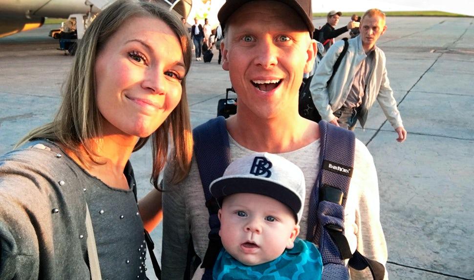Revista BABYBJÖRN – Vacaciones con niños: Petra Månström viaja con bebé, aquí está con su pareja que sostiene al bebé en una mochila porta bebé.
