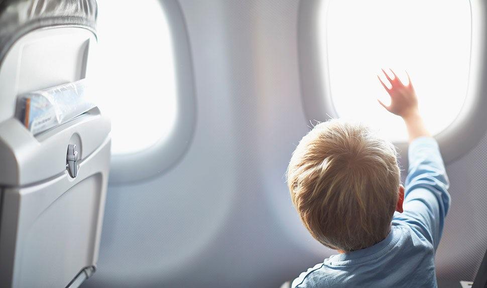 Revista BABYBJÖRN – Viajes con bebés: un bebé mirando por la ventanilla de un avión y señalando con el dedo.