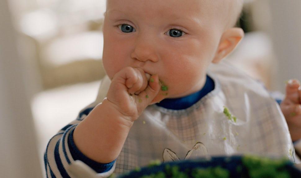 BABYBJÖRN Föräldramagasin – Barnmat till en bebis som kladdar vid bordet när hen äter.