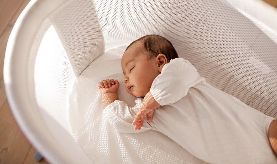 BABYBJÖRN Föräldramagasin – Spädbarn sömn, en nyfödd sover rofyllt i en vagga.