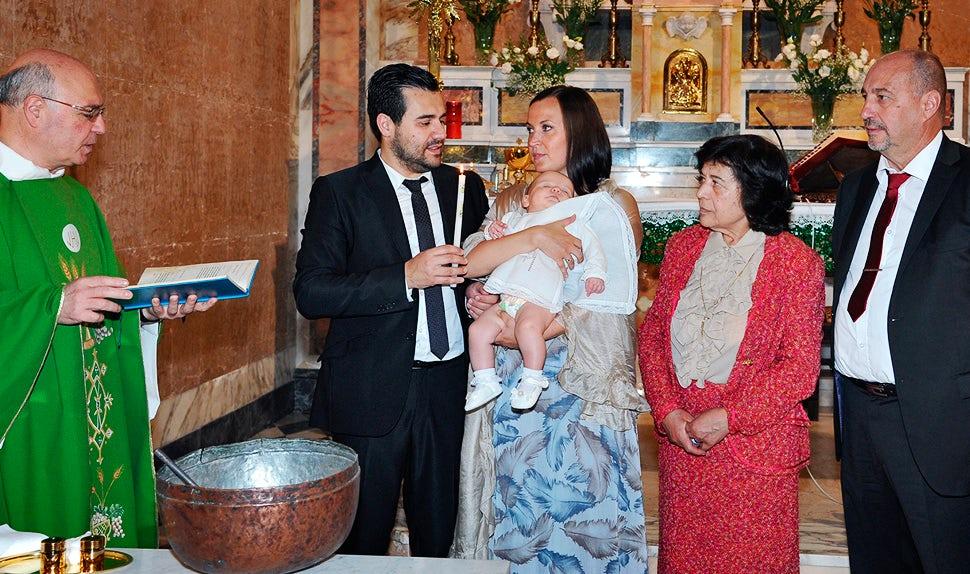 BABYBJÖRN Elternmagazin – Kirchliche Taufe der Tochter, der Priester gibt Wasser auf ihren Kopf.
