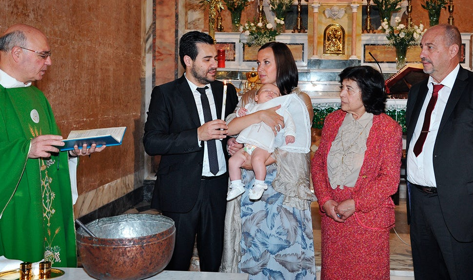 BABYBJÖRN Parental Magazine – Daughter's baptism in church; the priest pours water on her head.