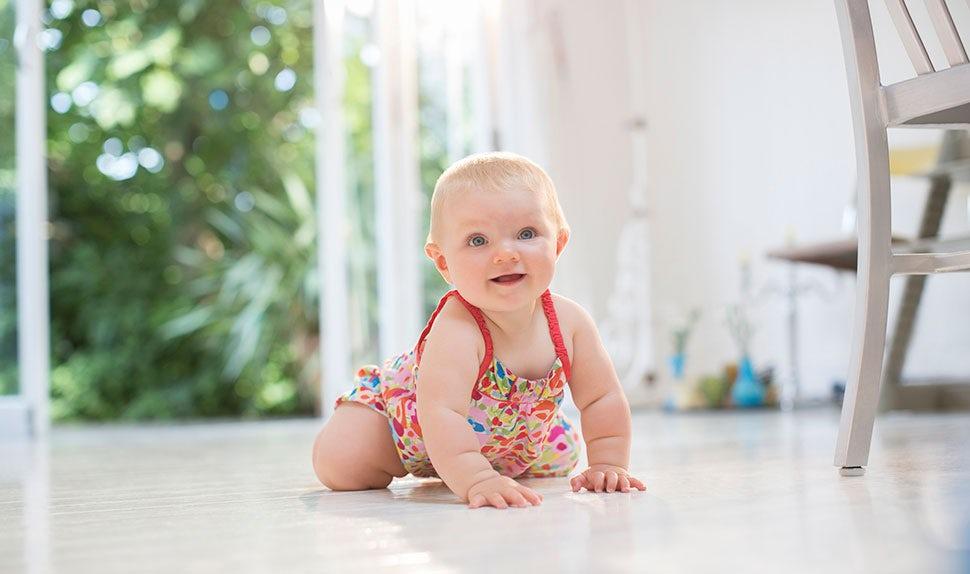 BABYBJÖRN Magazin – Wann lernt ein Baby krabbeln? Ein kleines Kind, das krabbeln, rollen und vorwärtsrobben lernt.