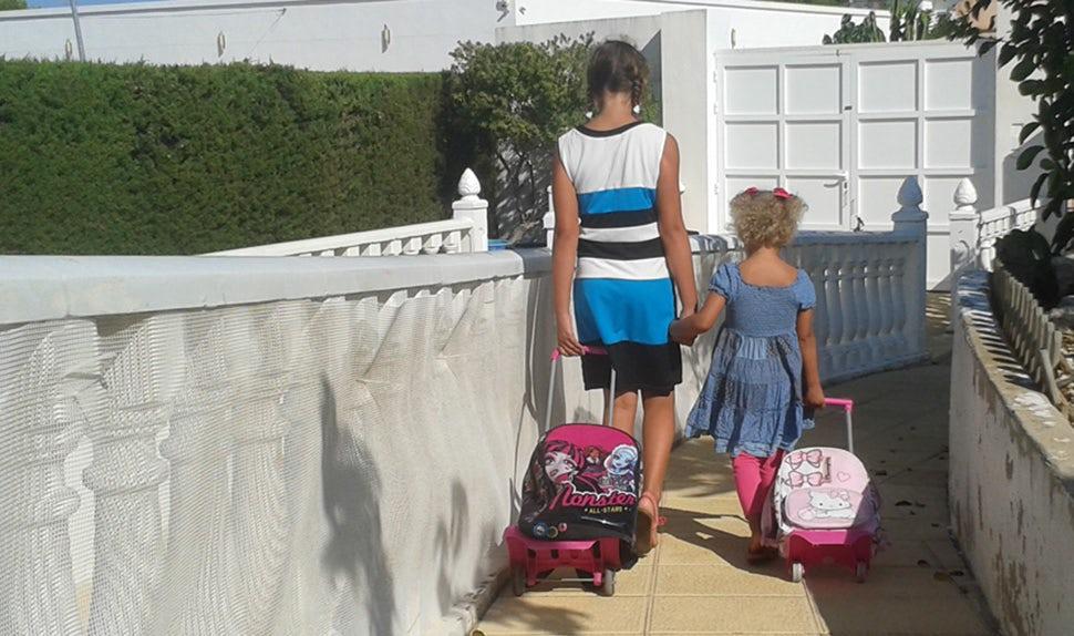 BABYBJÖRN Elternmagazin – Mit ihrer Familie zog Karin nach Spanien; Kinder mit Reisetaschen.