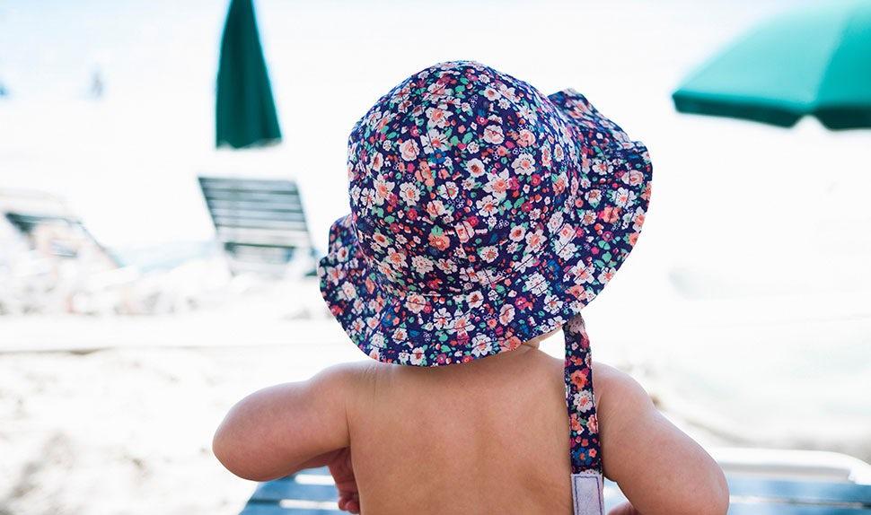 BABYBJÖRN Magazin – Kinder am Strand mit Sonnenhüten – ein Urlaub mit Kindern ist fantastisch.