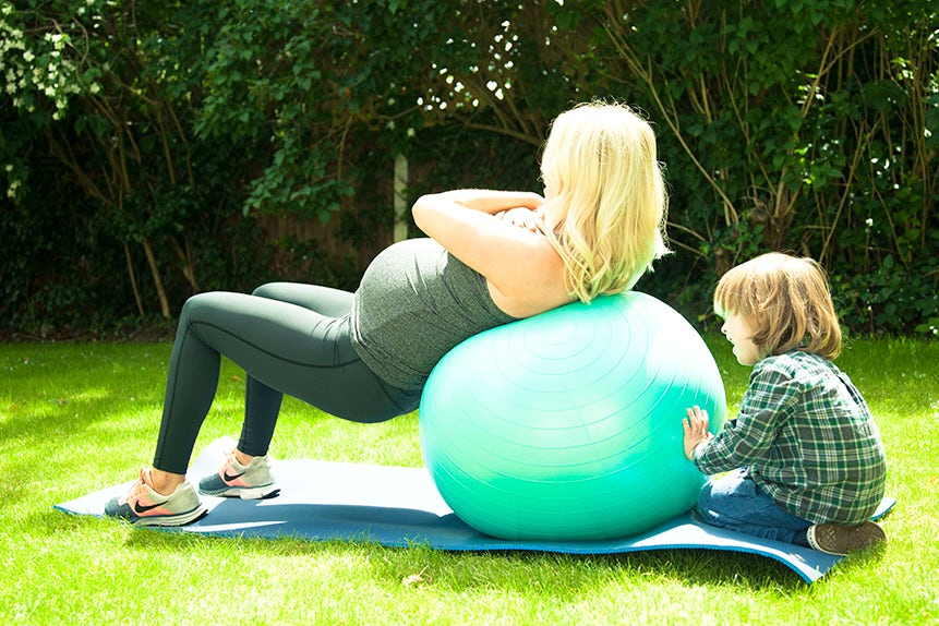 BABYBJÖRN Magazine for Parents – Pregnancy exercise: Alicia Irvine-MacDougall works out with a medicine ball in her garden.