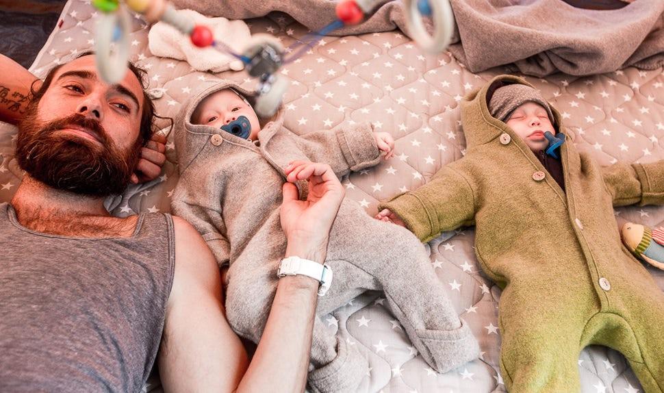 BABYBJÖRN Föräldramagasin – Pappa Christian tar det lugnt på en filt bredvid sina tvillingdöttrar.