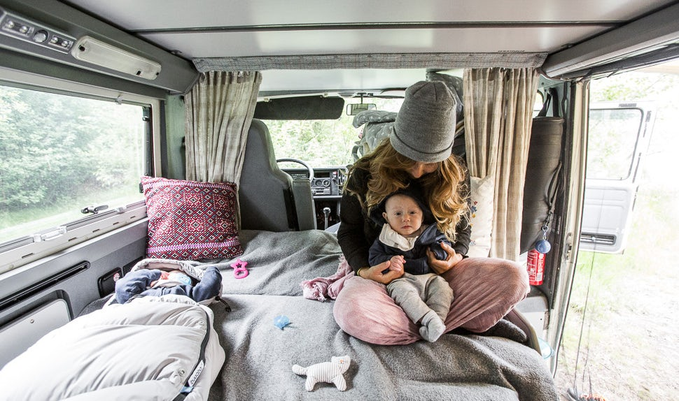 BABYBJÖRN Magazine for Parents - Mom Juli with one of the babies in her lap in the camper van.