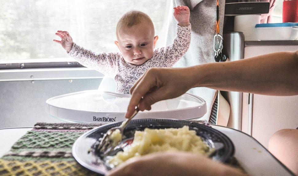 BABYBJÖRN Föräldramagasin – En av bebisarna sitter i matstolen och tittar förväntansfullt på maten som förbereds.