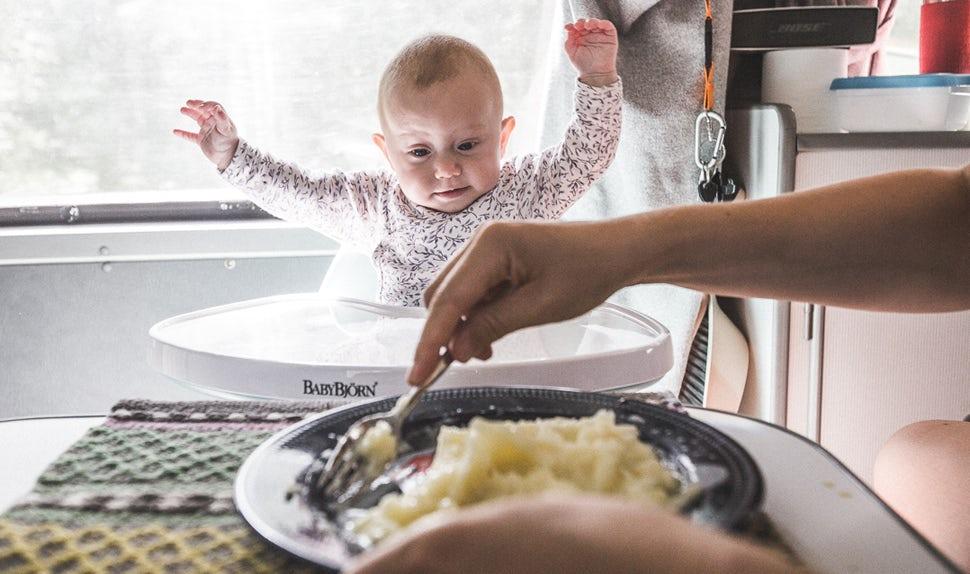 Magazine BABYBJÖRN – L'un des bébés assis dans une chaise haute observe avec intérêt la préparation du repas.