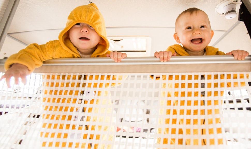 Magazine BABYBJÖRN – Les deux jumelles joyeuses sont debout sur le lit près du filet de sécurité.