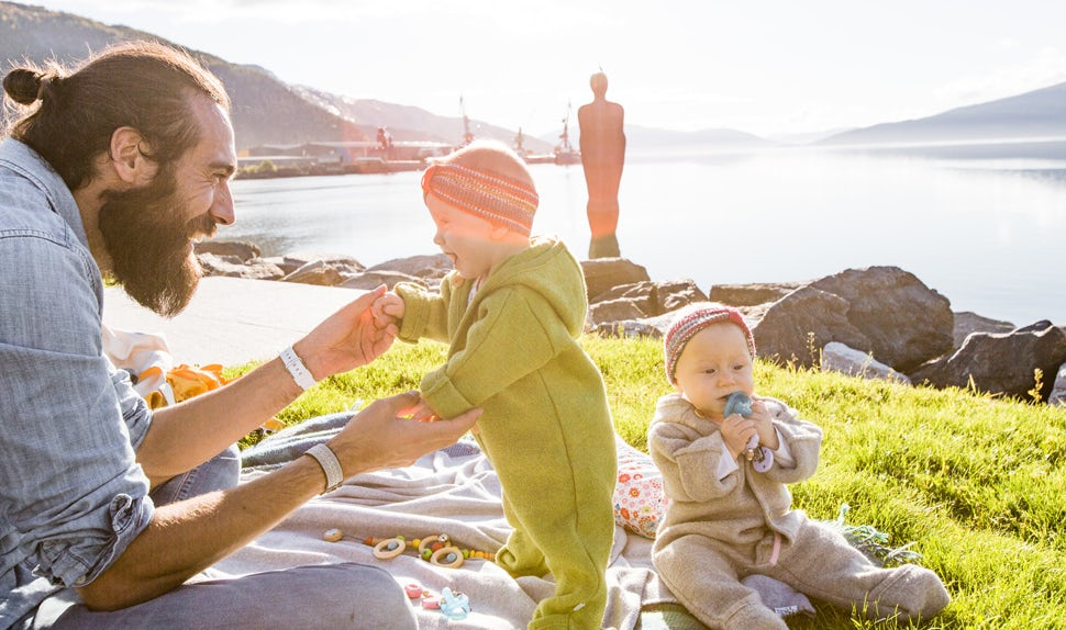 BABYBJÖRN Magazine – In the sunshine, the Smuts spend quality time with their dad on a blanket on the grass.