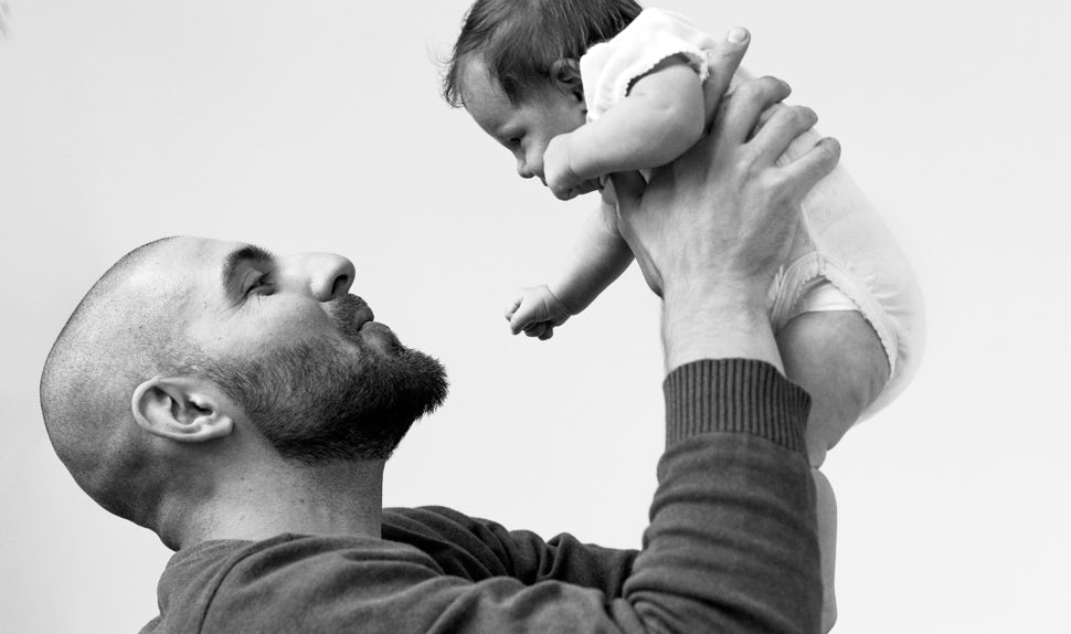 BABYBJÖRN Magazine – Dadstories: Pierre holds his daughter Olivia in his arms.