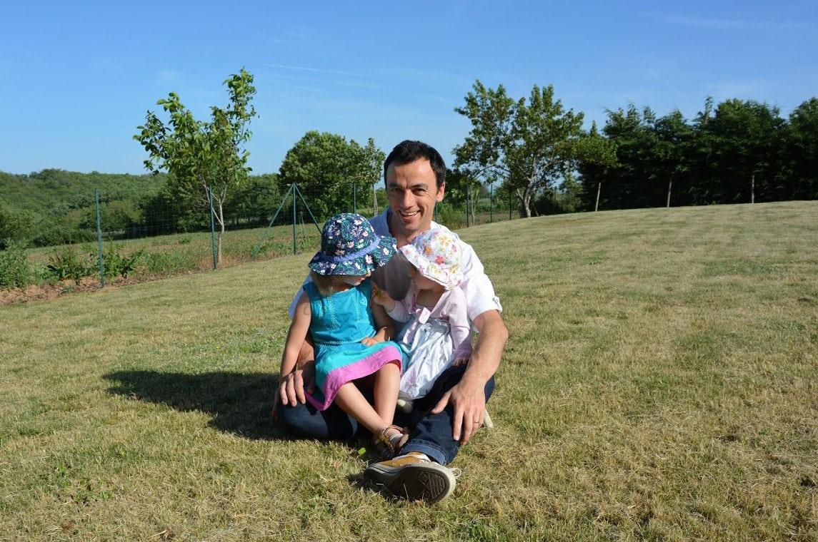 Revista BABYBJÖRN Föräldramagasin – El sol brilla y papá Pierre está sentado en la hierba con sus dos hijas en las rodillas.