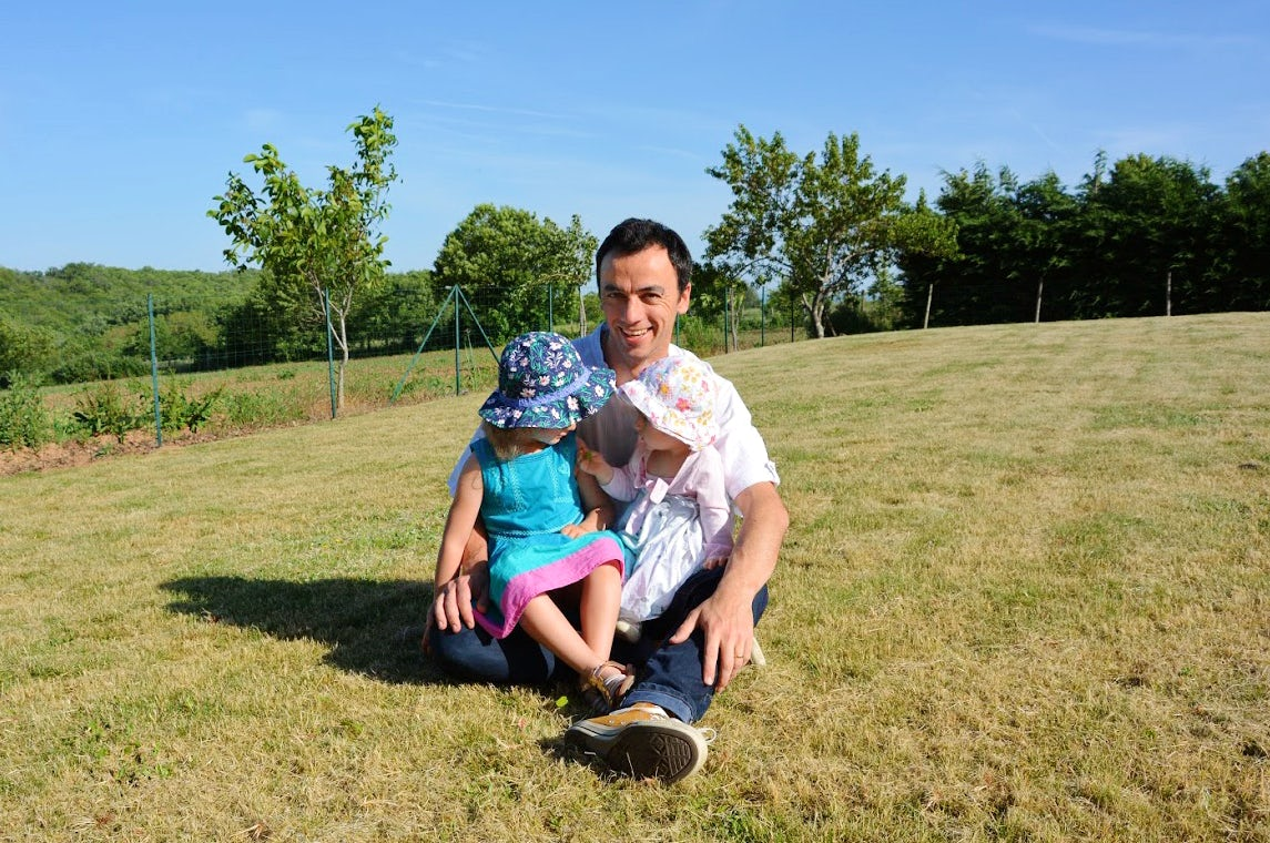 BABYBJÖRN Magazine – The sun is shining and dad Pierre is sitting on the grass with his two daughters.