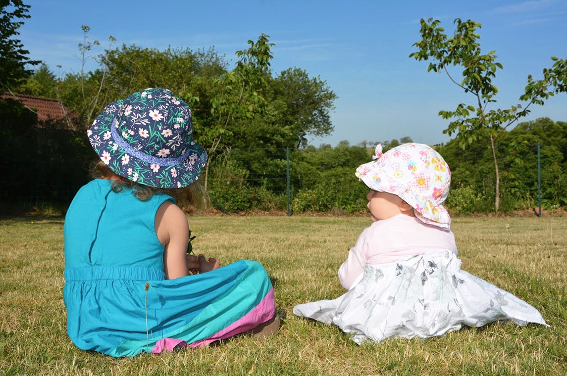 BABYBJÖRN Magazine – Sisters Luna and Maëlie sitting on the grass with their backs to the camera.