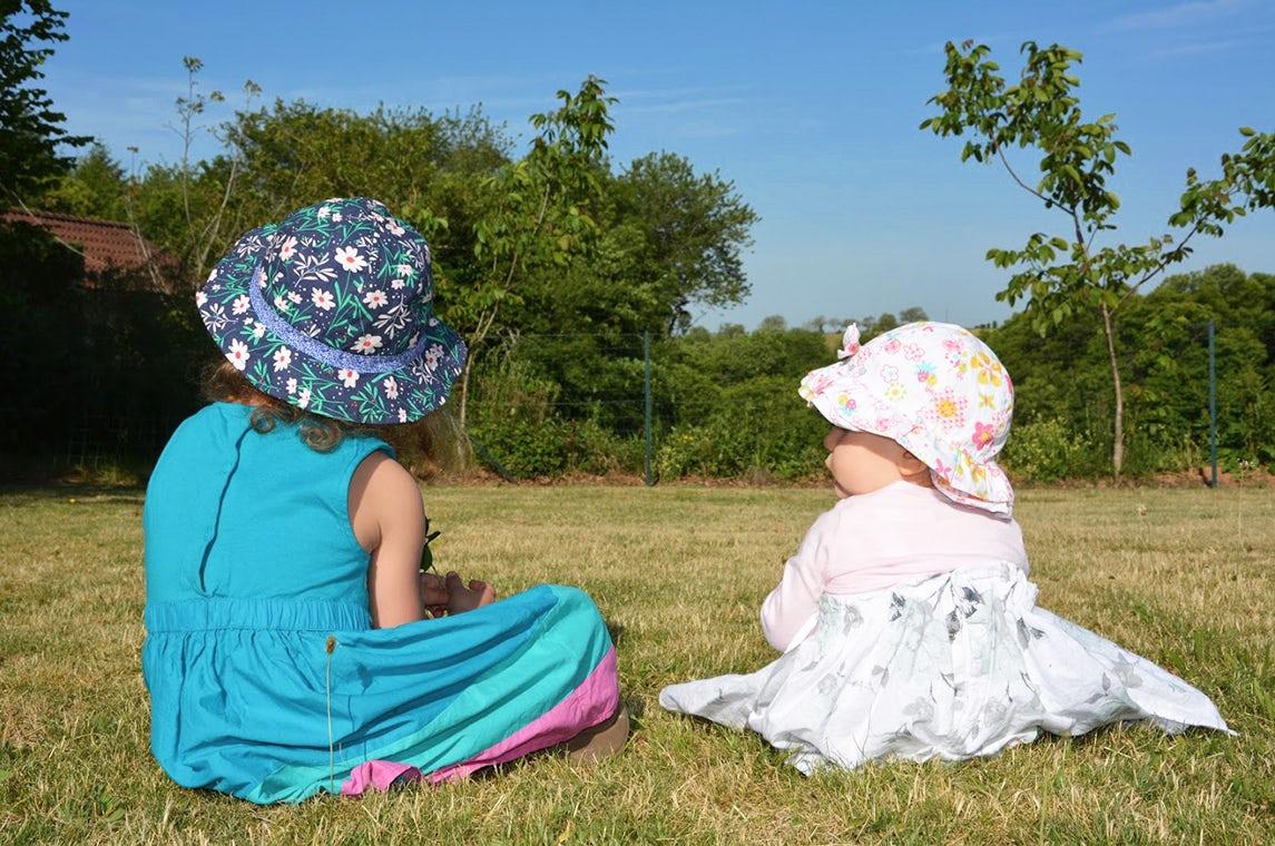 Revista BABYBJÖRN – Las hermanas Luna y Maëlie sentadas juntas en la hierba, de espaldas a la cámara.