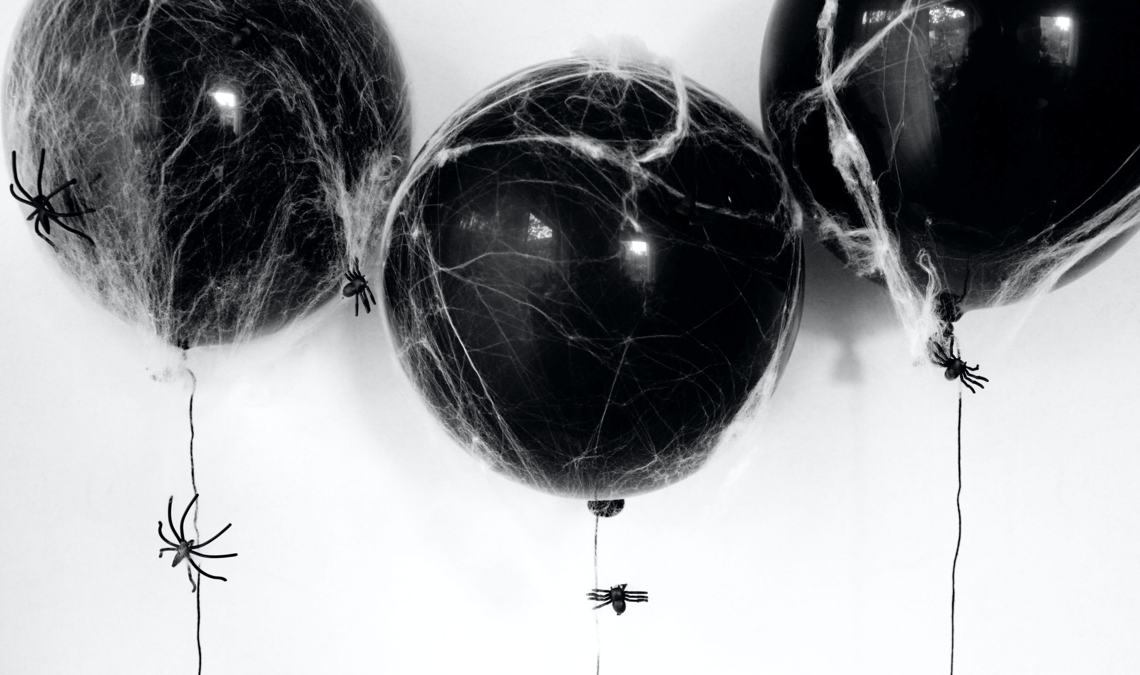 BABYBJÖRN Magazine – DIY Halloween decorations: Black balloons with spider web and plastic spiders.