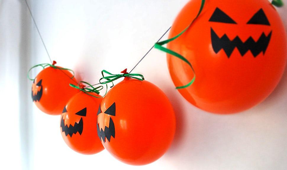 BABYBJÖRN Magazin – Eine Girlande aus orangefarbenen Ballonkürbissen als Halloween-Deko.