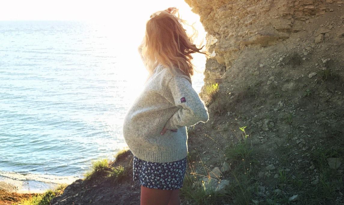 BABYBJÖRN Magazin – Klara Svensson, hier noch mit Babybauch, sieht aufs Meer hinaus. Sie bereitete sich mit Hypnobirthing auf die Geburt ihres Sohnes vor.