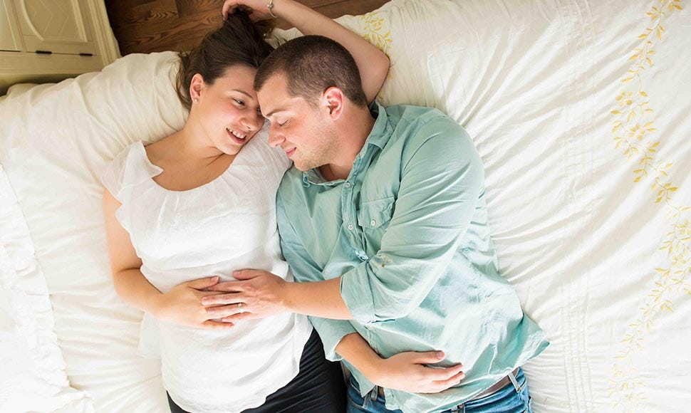 BABYBJÖRN Föräldramagasin – Gravid kvinna och man i en säng samtalar om barnet i magen.