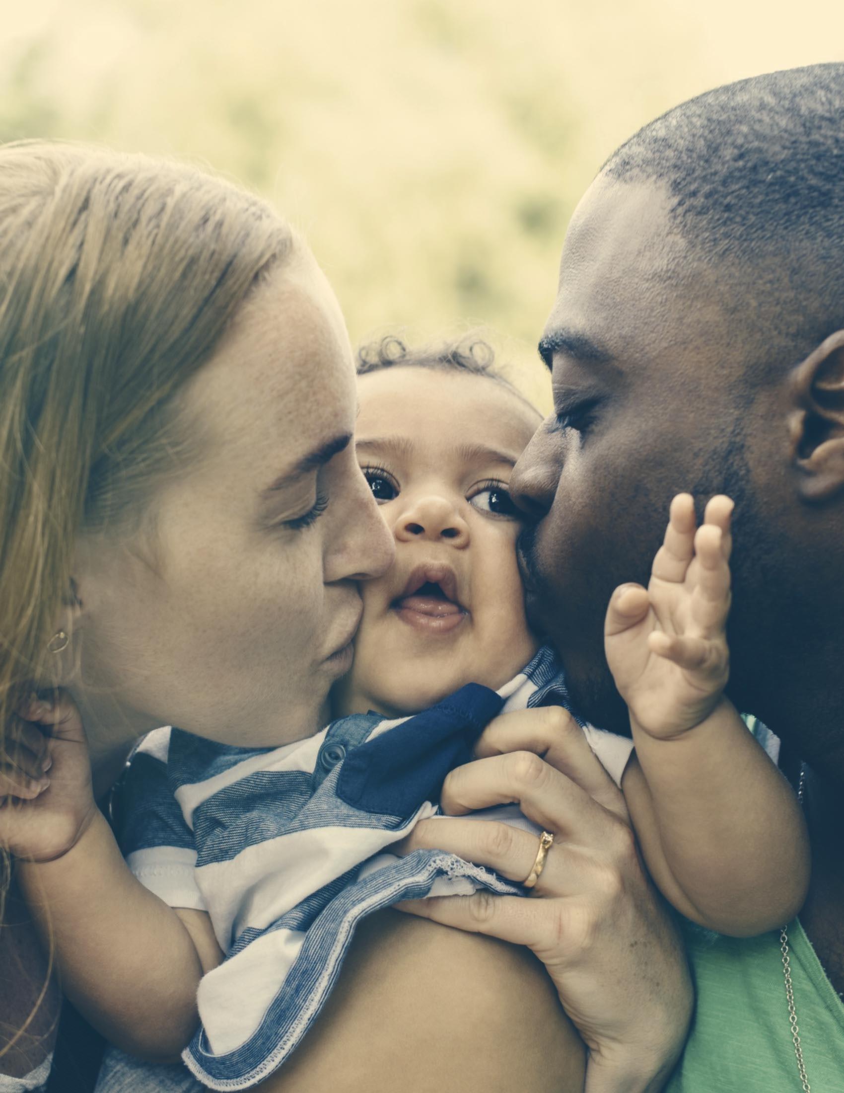 Bebis blir pussad på kinderna av sina föräldrar   BABYBJÖRN