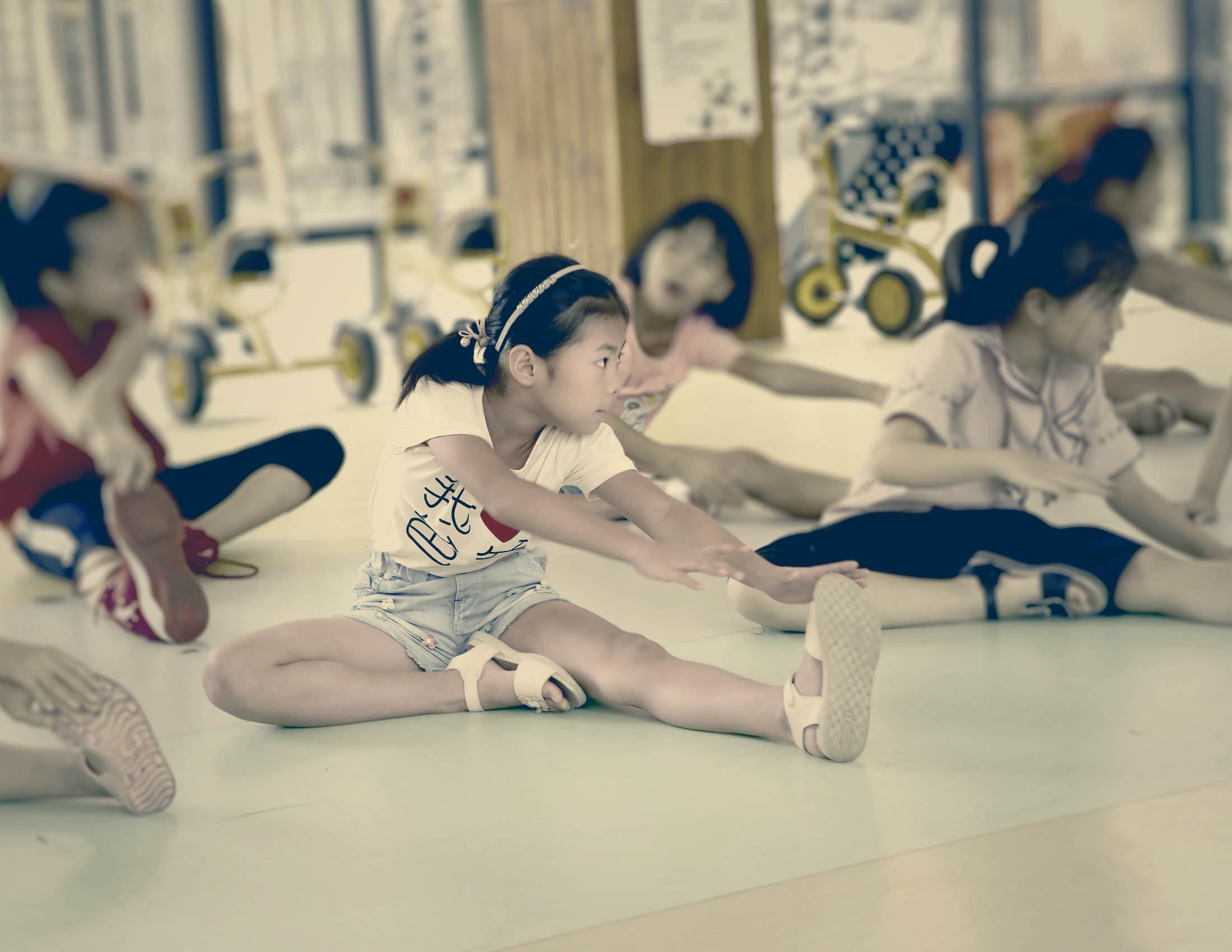 Photo de Mor Lee faisant des exercices d'étirement sur le sol avec d'autres enfants | BABYBJÖRN