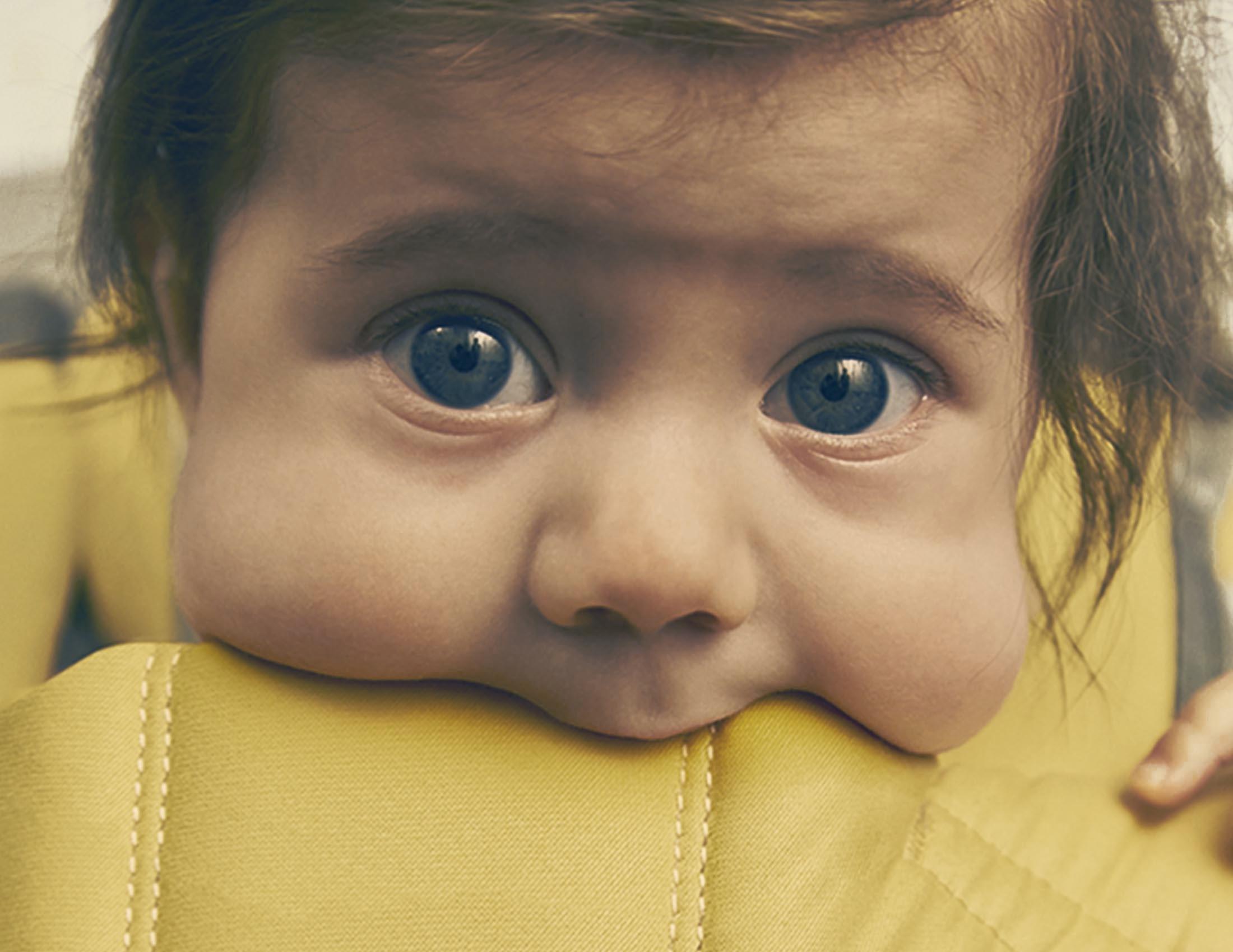 Un bébé mâchouillant le bord du Porte-bébé One de BABYBJÖRN
