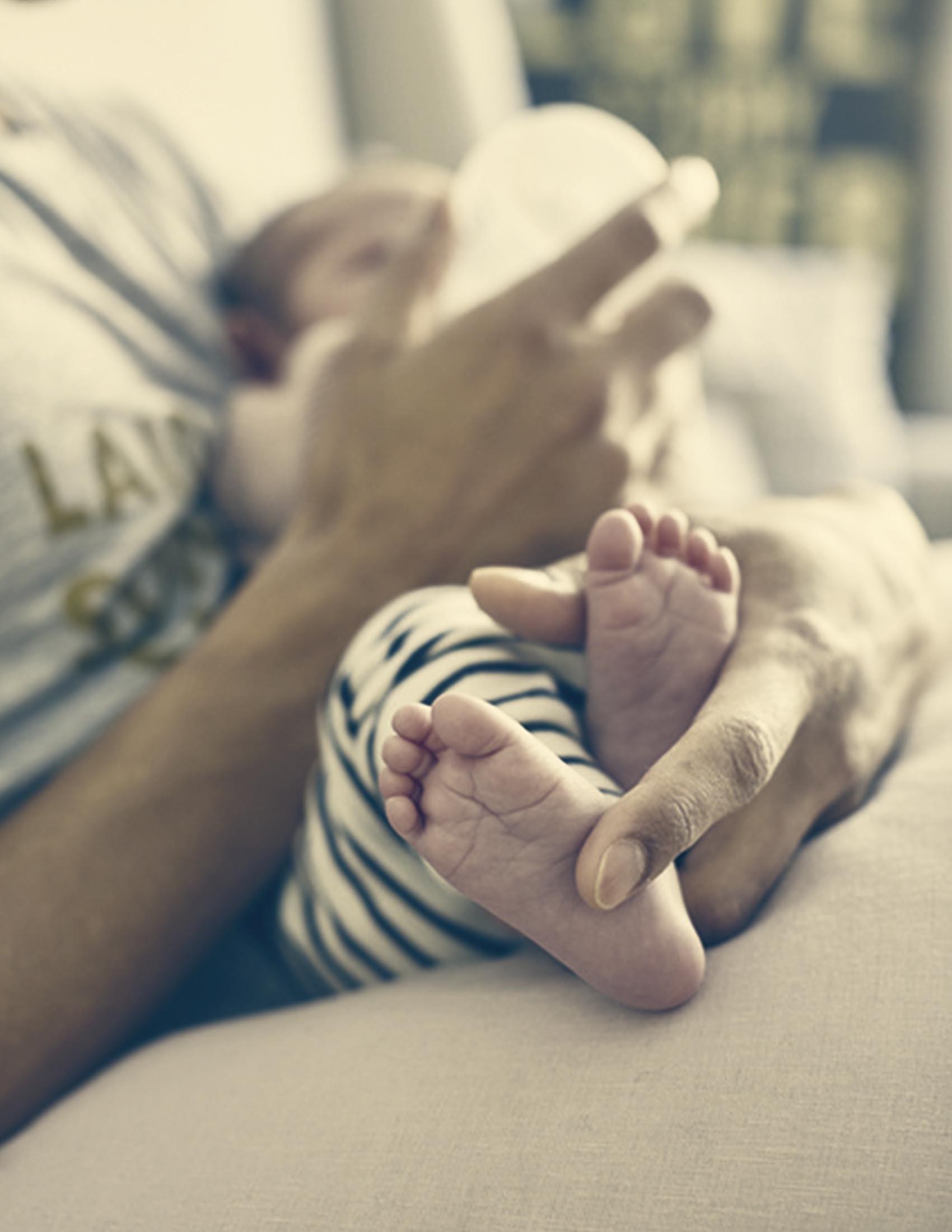 Kleines Baby auf dem Arm wird mit Fläschchen gefüttert | BABYBJÖRN
