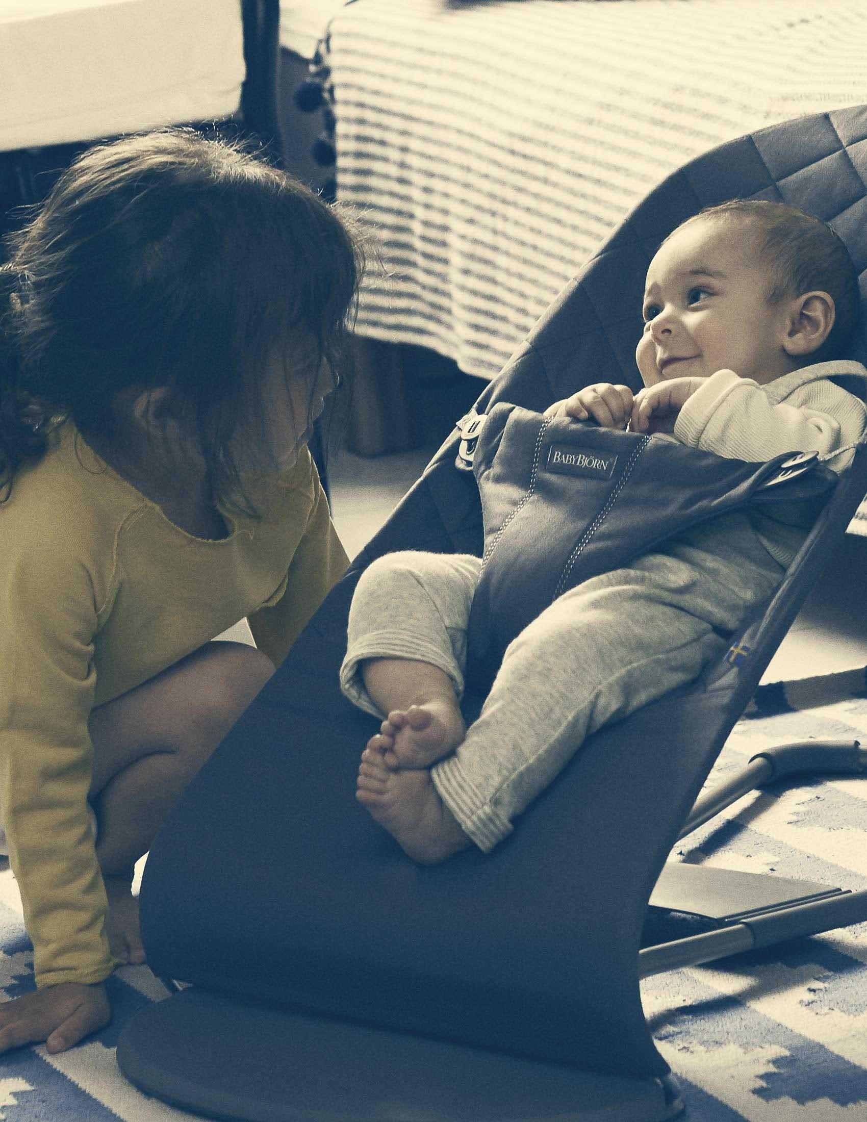 Baby sitzt in der Babywippe Bliss von BABYBJÖRN, Schwester hockt daneben auf dem Boden | BABYBJÖRN