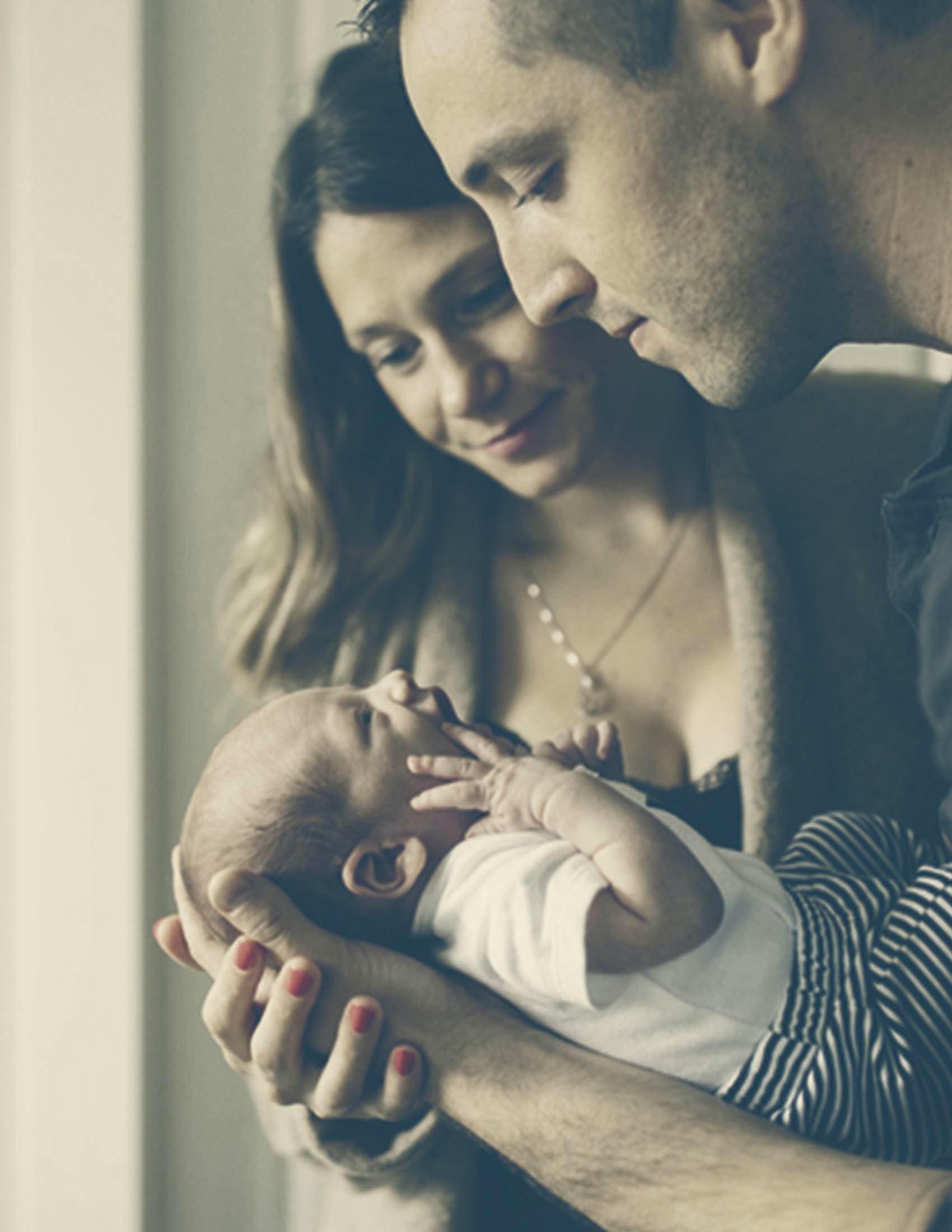 Dos padres sostienen y miran a su bebé | BABYBJÖRN