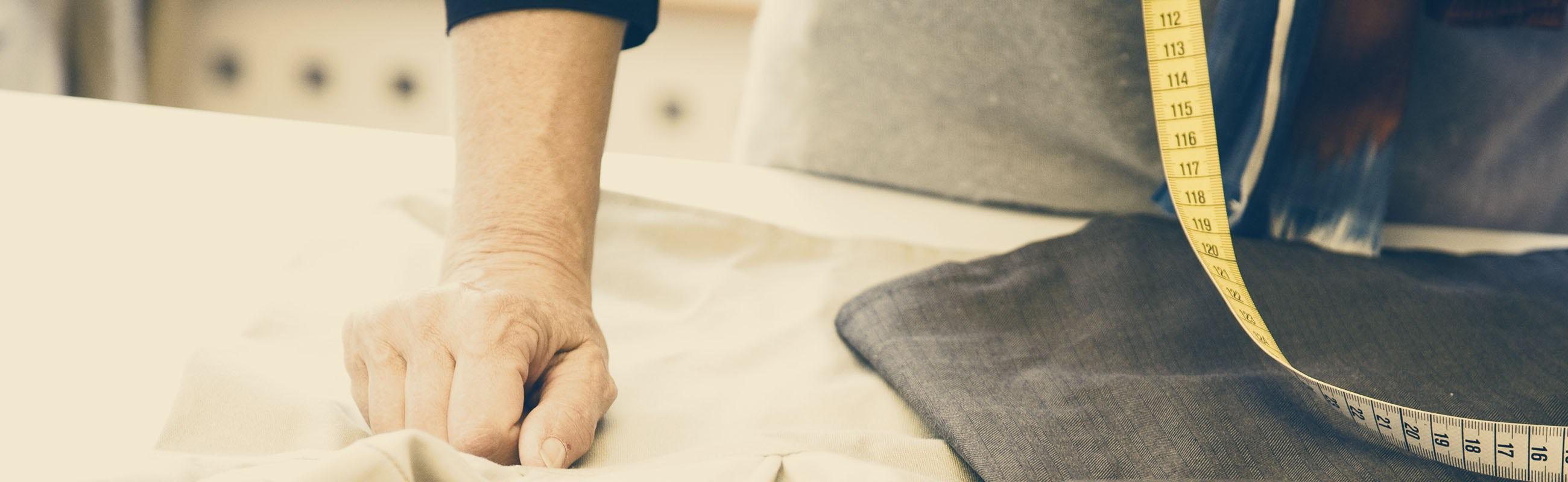 Primer plano de las manos de Lisen, nuestra diseñadora textil, con tijeras y cortador para patrones| BABYBJÖRN