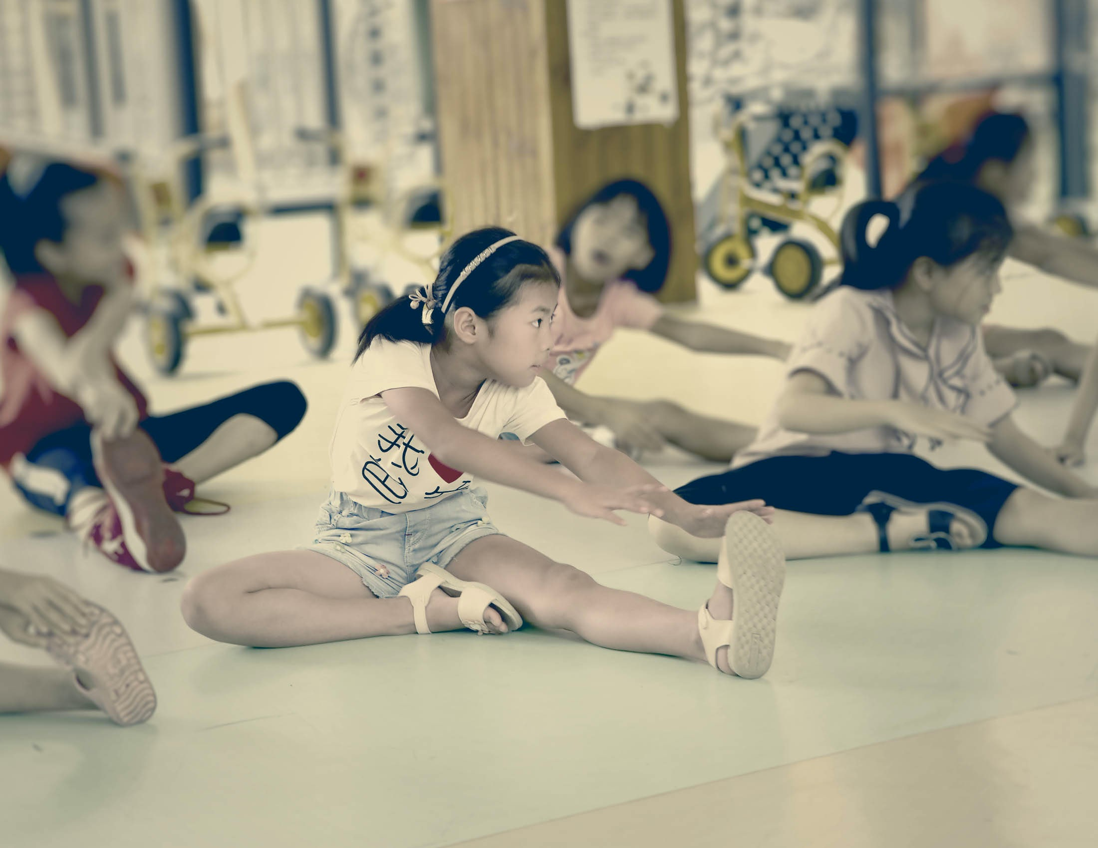 Picture of Mor Lee and other children performing stretching exercises on the floor | BABYBJÖRN