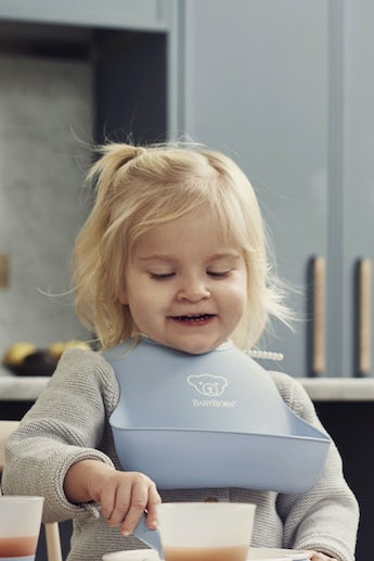 Baby bib 2-pack in green and blue BPA-free plastic with big pocket for food that does not make it to the mouth